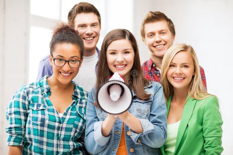 小组有扩音机的学生在学校 免版税图库摄影