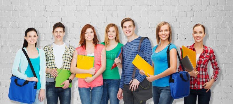 小组有文件夹和袋子的少年学生 库存图片