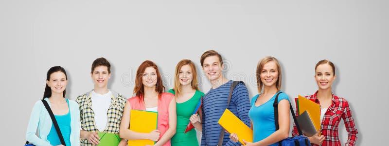 小组有文件夹和袋子的少年学生 免版税库存照片