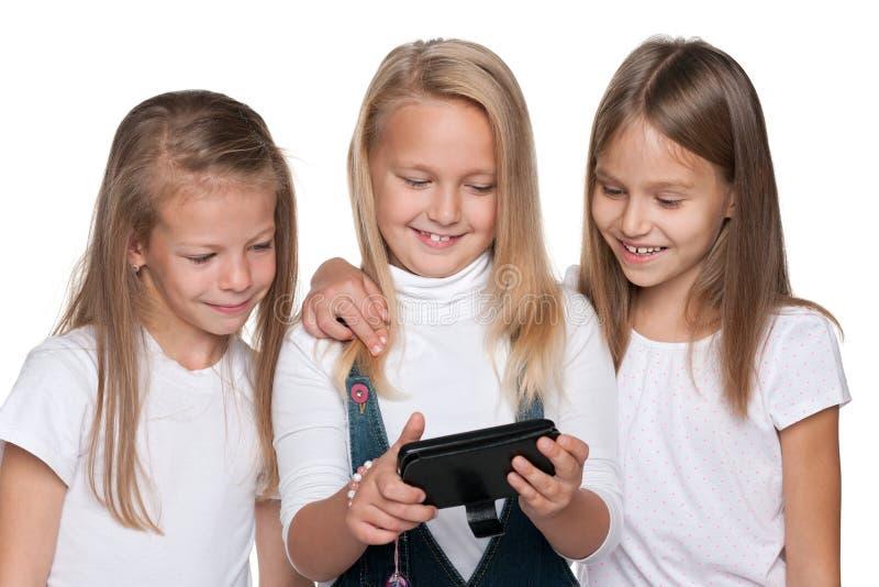 小组有智能手机的女孩 库存图片