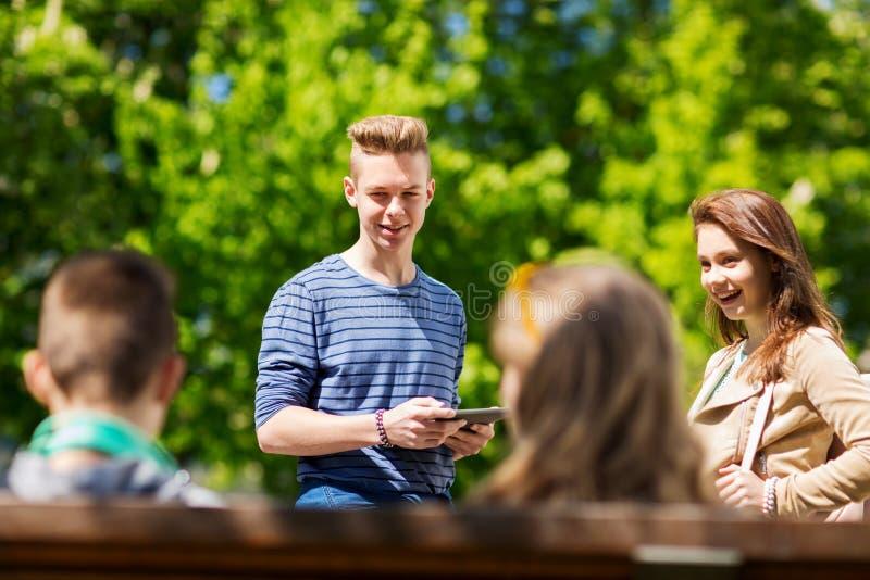 小组有片剂个人计算机outoors的少年学生 免版税图库摄影