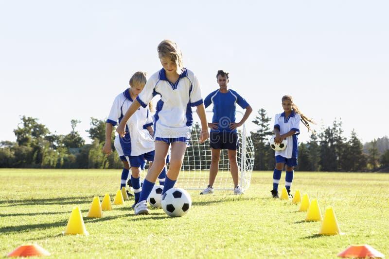小组有的足球队员的孩子与教练的训练 库存照片