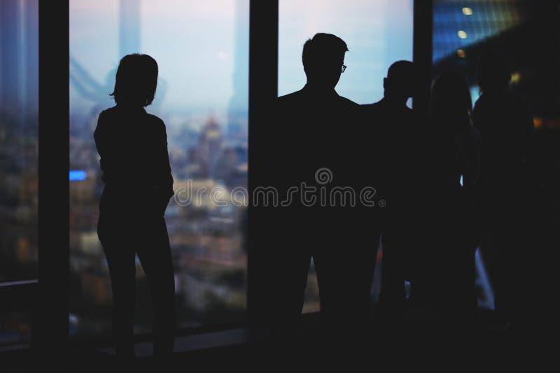 小组年轻有目的金融家的剪影带领一次交谈,当站立在现代办公室内部时 库存照片