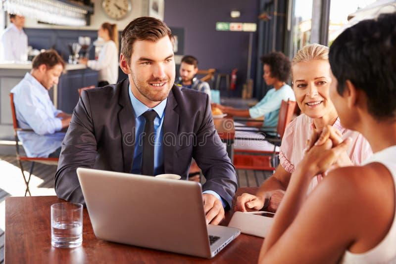 小组有膝上型计算机会议的商人在咖啡店 库存照片