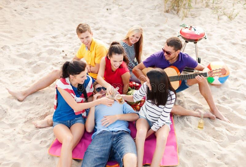 小组有获得的吉他的朋友在海滩的乐趣 免版税库存图片