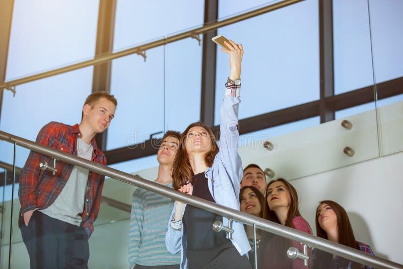 小组有采取selfie的智能手机的微笑的学生 免版税库存图片
