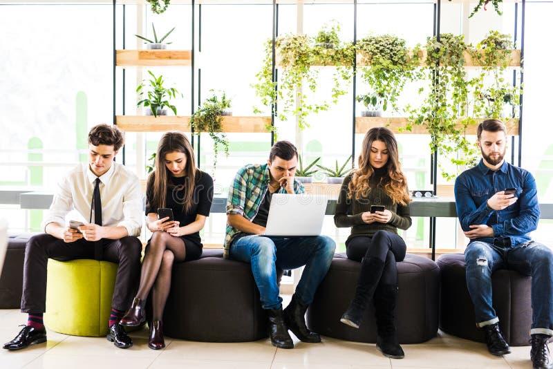 小组朋友坐椅子在彼此和大家附近用途他的divices在现代办公室室 同时在设备的乐趣 库存照片