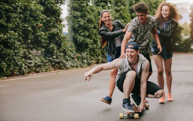小组朋友获得乐趣户外与滑板 库存图片