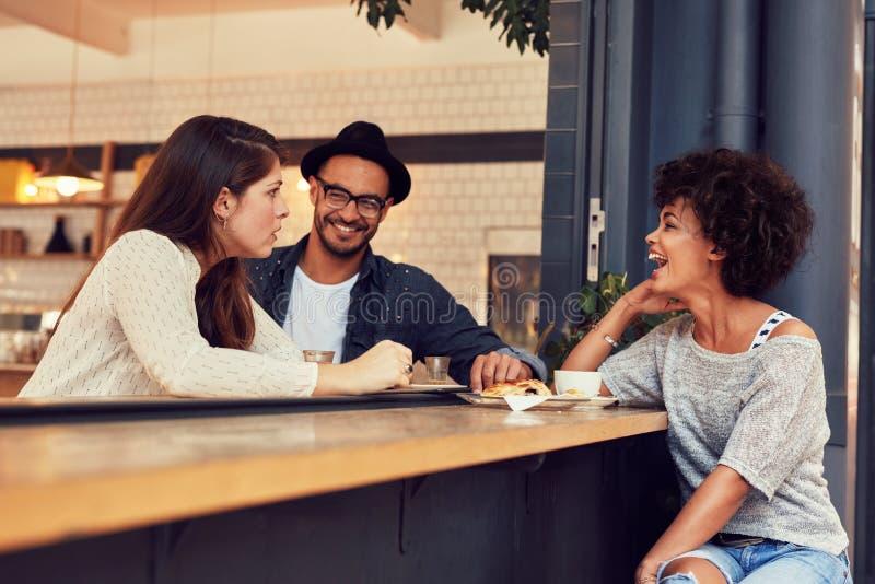 小组朋友谈话在咖啡馆 免版税库存照片