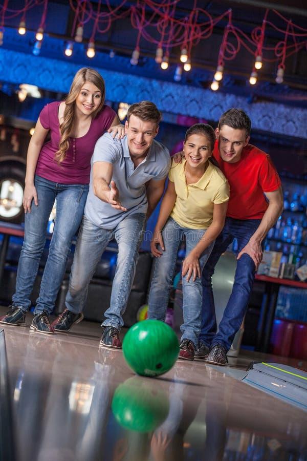 小组朋友滚保龄球。 免版税图库摄影