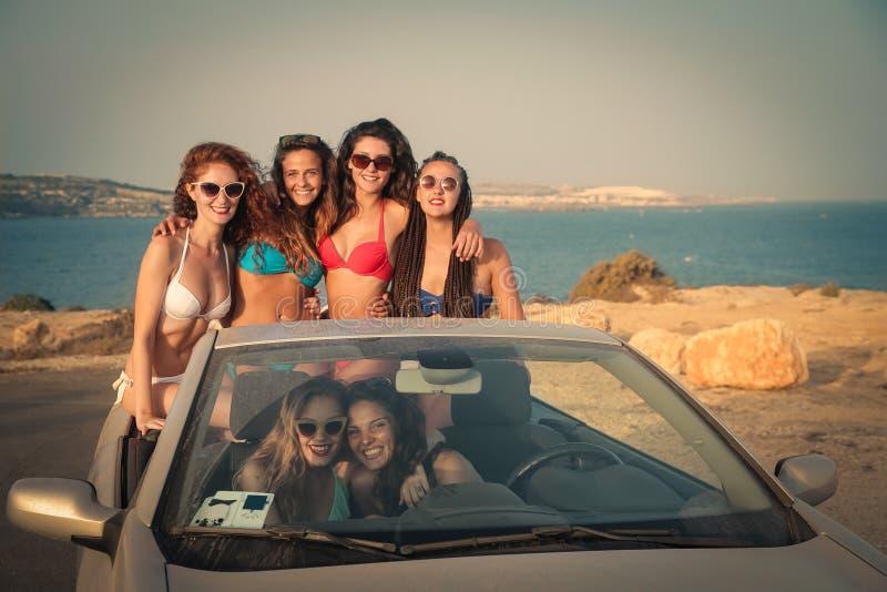 小组海滩的女孩与汽车 免版税库存照片