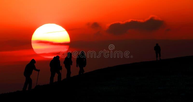 小组游人采取对山在日落。剪影 免版税库存图片