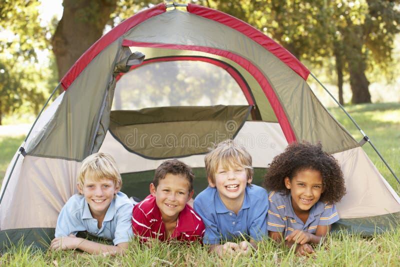 小组男孩获得乐趣在帐篷在乡下 免版税库存图片