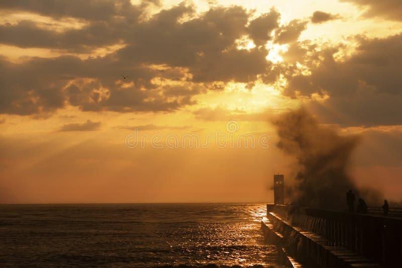 小组码头的渔夫在有波浪飞溅的灯塔附近 免版税图库摄影