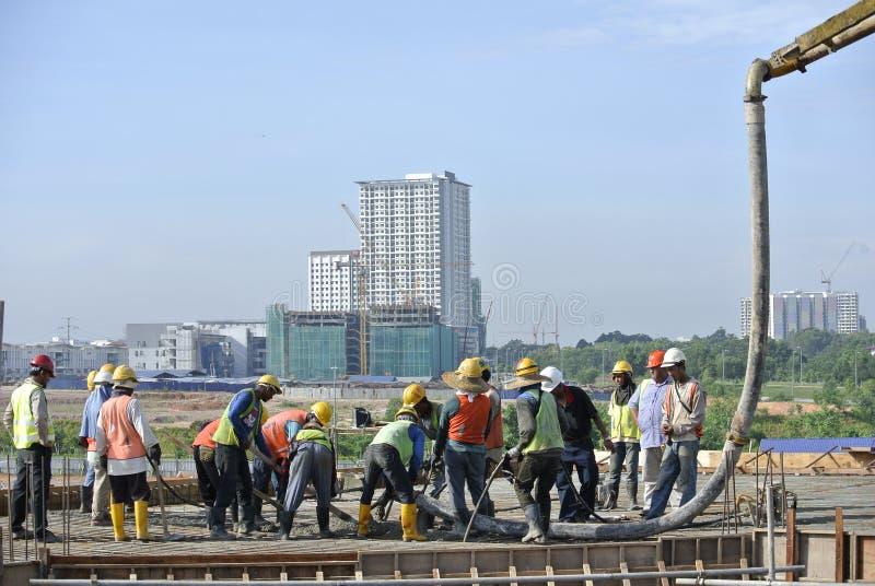 小组建筑工人和混凝土泵 免版税库存图片