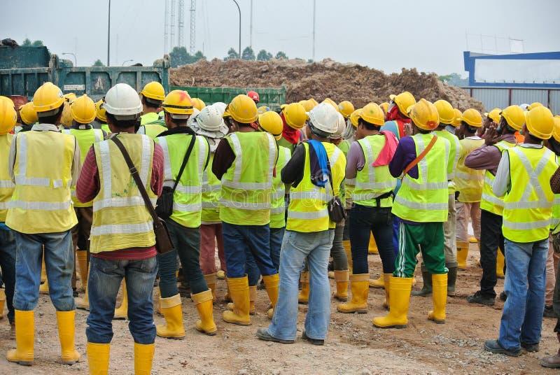 小组建筑工人聚集在露天场所 免版税库存照片