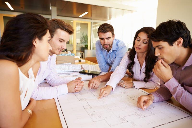 小组建筑师谈论计划在现代办公室 图库摄影