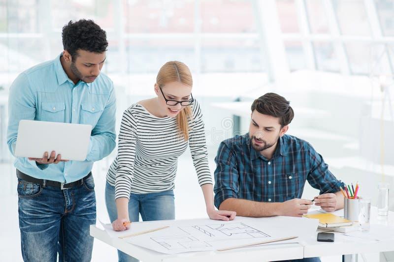 小组建筑师谈论计划在现代办公室 免版税库存图片
