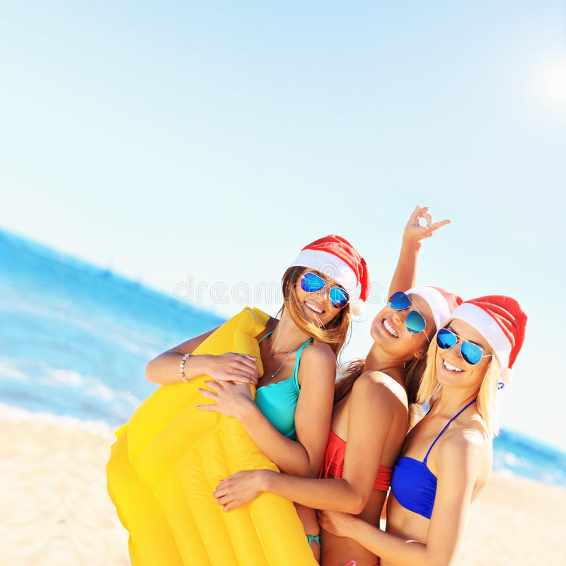 小组获得圣诞老人的帽子的女孩在海滩的乐趣 库存图片