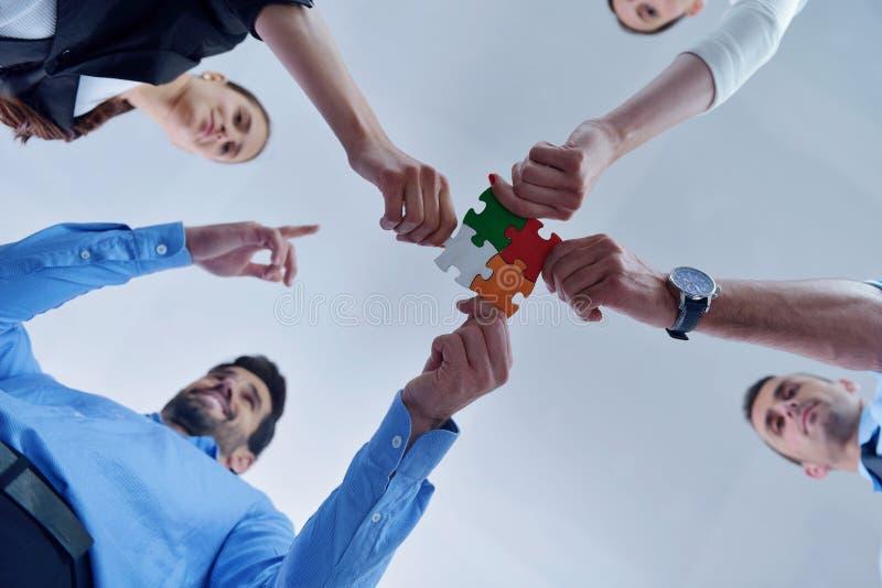 小组装配七巧板的商人 免版税库存图片