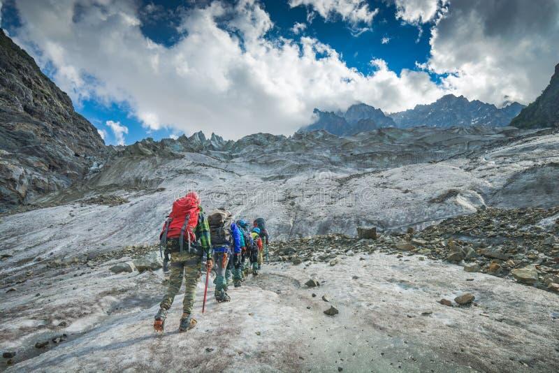 小组远足者攀登冰川 免版税库存照片