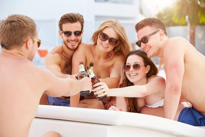 小组青年人在度假放松由游泳池的 库存图片