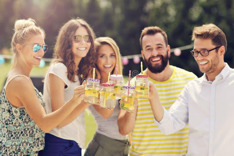 小组青年人欢呼和获得乐趣户外与饮料 库存照片