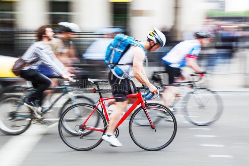 小组骑自行车者在行动迷离的城市 库存图片