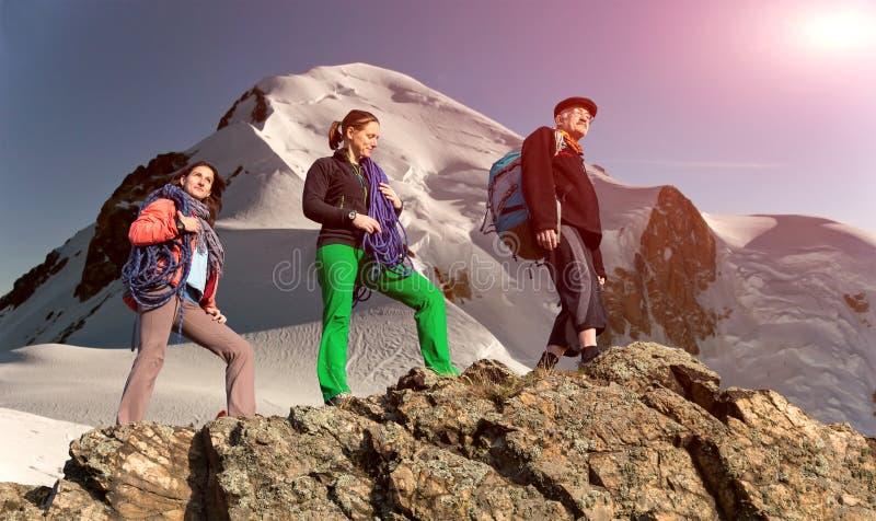 小组高山背景的登山人 免版税图库摄影