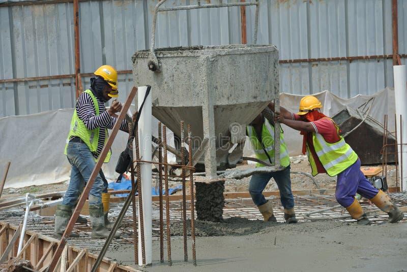 小组concreting平板的建筑工人在建造场所 库存图片