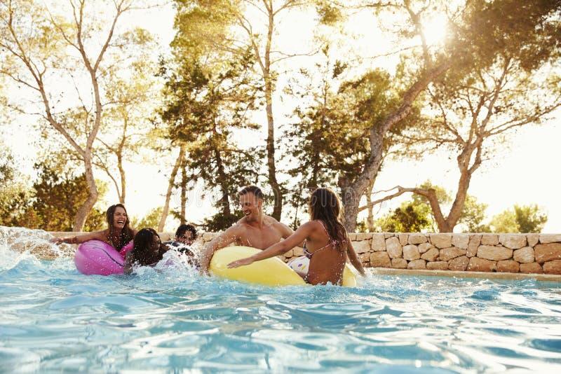 小组Inflatables的朋友在室外水池 免版税库存图片