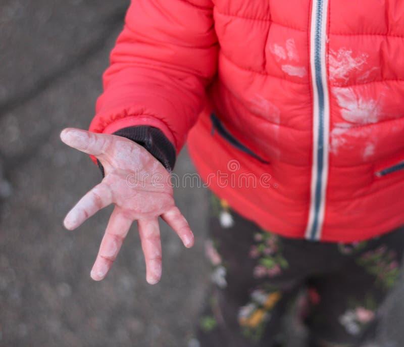 小children& x27;在沥青背景的上面被伸出的s肮脏的手胳膊 免版税图库摄影