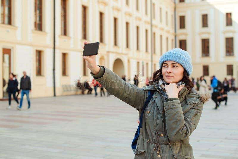 少女与电话的作为selfie在城市街道上 微笑和做旅行selfie的妇女游人 享受假期的愉快的女孩 免版税库存照片