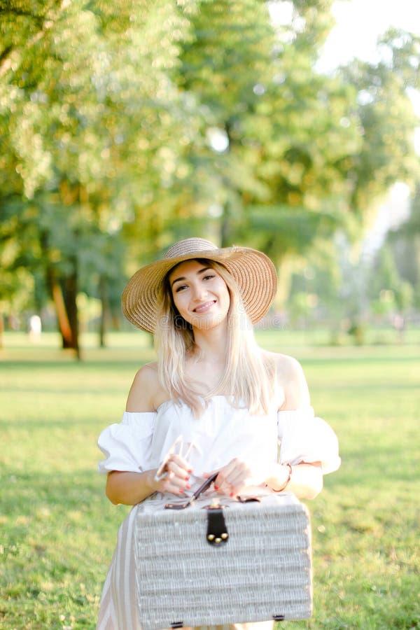 少女佩带的帽子身分在有袋子的公园 免版税库存照片