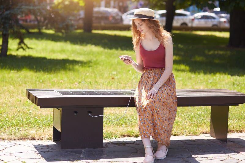 少女充电手机的图象通过户外USB,在长凳的女性开会与太阳电池板在镇公园 公开充电 图库摄影