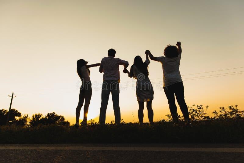 少女公司和人在草站立在路附近在一个夏日并且握他们的手 免版税图库摄影