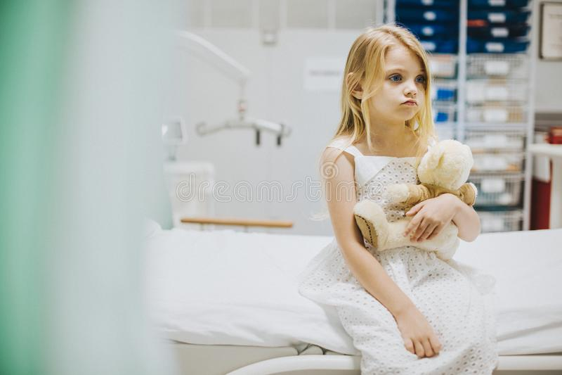 少女单独坐医院病床 库存图片