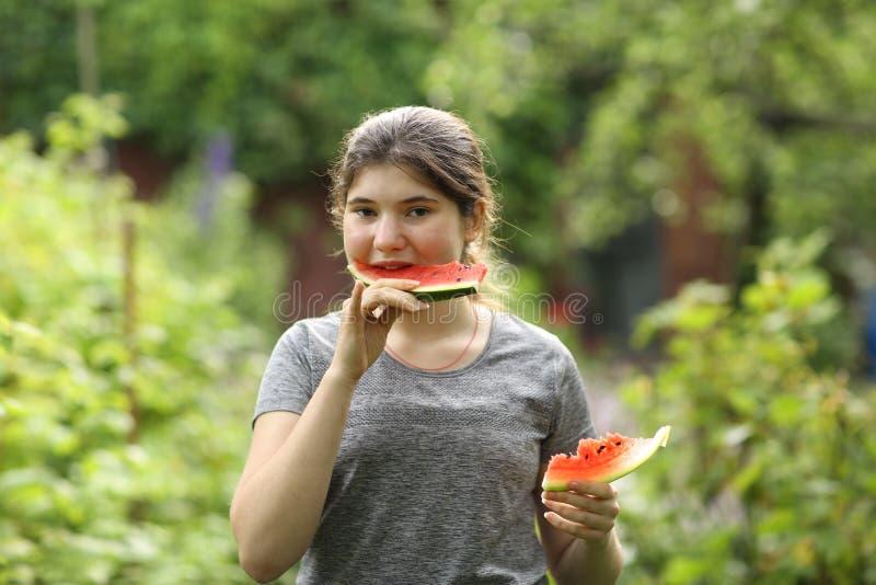 少女吃切西瓜片贴合照片 库存照片