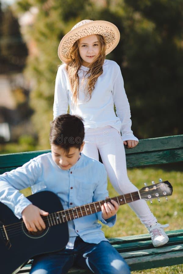 少女和男孩有坐在长凳的吉他的在公园 儿童爱 免版税库存照片