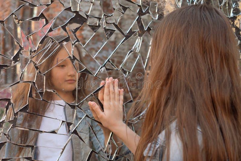 少女在一个残破的镜子看并且显示她的在镜子的手 免版税库存照片
