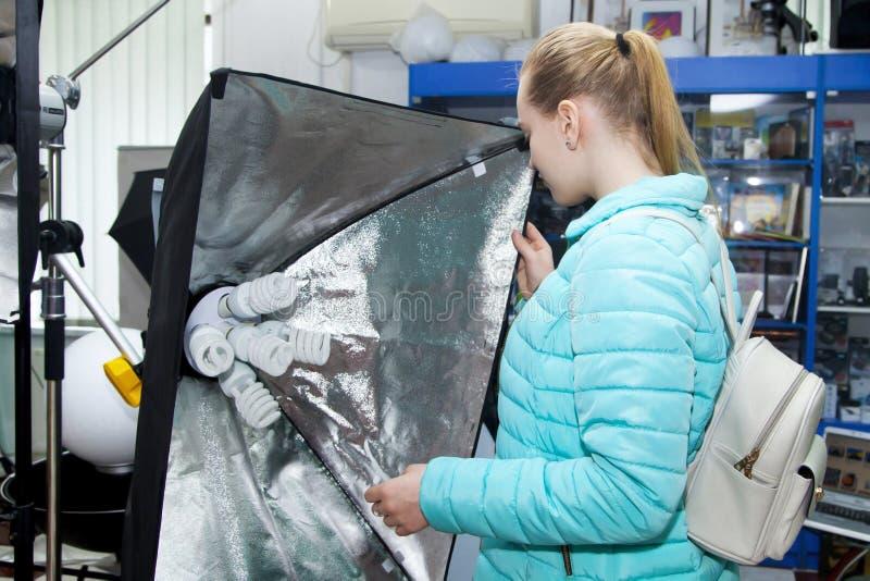 少女在专业照片设备商店选择永久演播室照片光灯与方形的反射器的 免版税库存图片