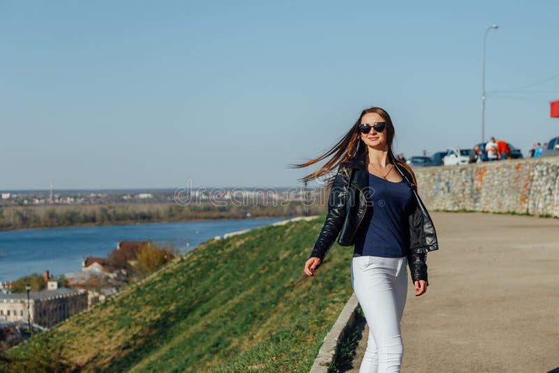 少女在城市海湾的堤防走 免版税图库摄影