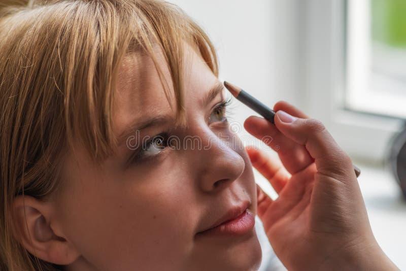 少女在她的有眉笔的眼眉被帮助投入构成 免版税图库摄影