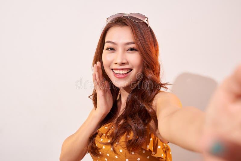 E 少女在现代智能手机前面照相机的作为selfie  图库摄影