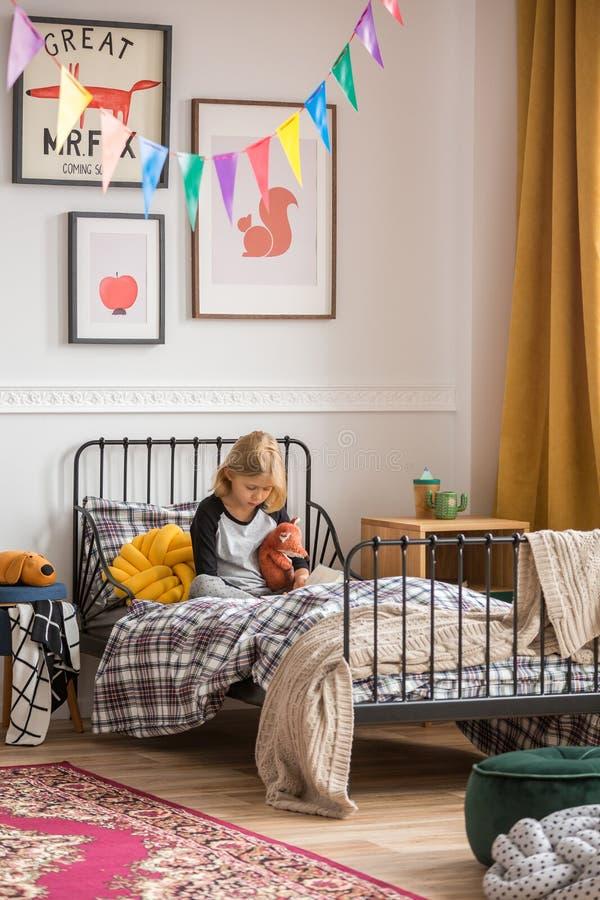 少女坐她的床在减速火箭的被称呼的室 免版税库存图片