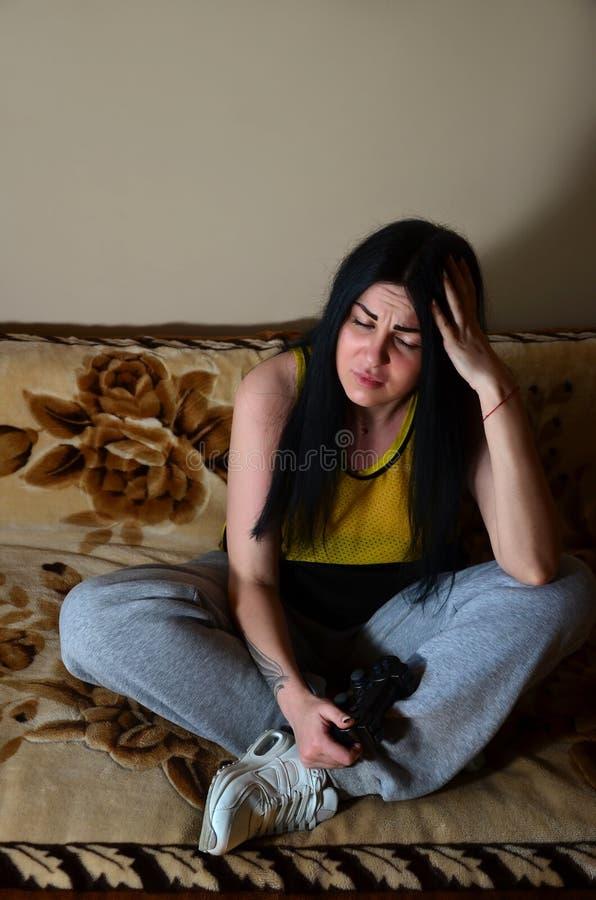 少女坐长沙发由损失失望 免版税库存照片