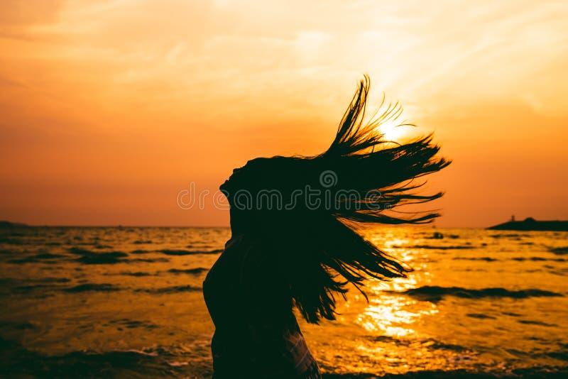 少女头发在夏天海日落背景的轻打飞溅剪影  图库摄影
