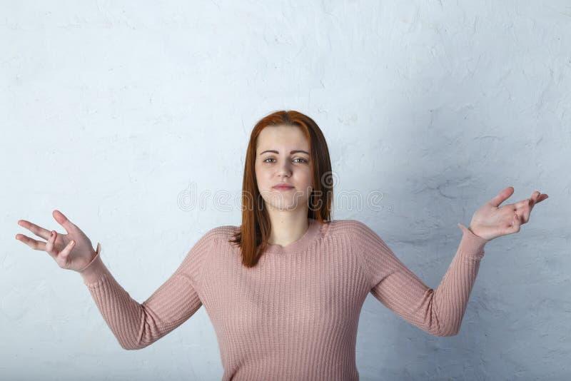 少女投掷他的在灰色背景,米黄定调子的手 免版税库存图片