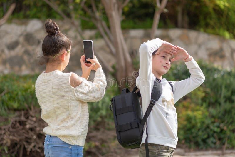 少女拍与室外的智能手机的一张照片 库存照片