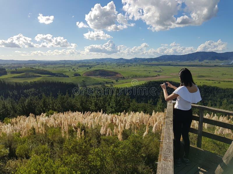 少女拍摄一个美好的风景视图的照片 免版税库存照片